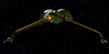 Forward shot of a starship in the black of space with distant stars in the background. The ship is primarily one color, save for a decorative pattern on its underside. The center portion of the ship is bulbous, with thin, down-stretched wings capped by long guns.