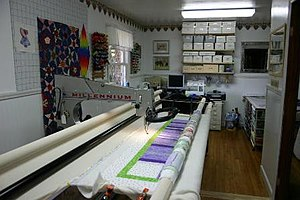 Longarm quilting -  A longarm sewing machine with a quilt top placed on the frame.