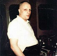 An overweight white male with shaved head and eyebrows, wearing a white short-sleeved shirt and black trousers, looks at the camera with a neutral expression.  The room behind him appears dark, and several unidentifiable pieces of equipment are visible.