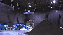 A studio sound stage, with a pile of mulch in the foreground and cherry pickers and a constructed mausoleum in the background.