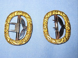 Breeches - A pair of buckles for dress breeches. The T-hook of the buckle is inserted into a buttonhole located on the strap at the bottoms of the leg of the breeches. The end of the strap is slipped through, the prongs lowered and then the end slipped through the otherside of the buckle.