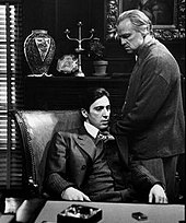 Uma captura de tela de Michael e Vito Corleone em O Poderoso Chefão