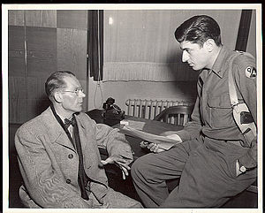 Fifteenth United States Army - S/Sgt. Ralph Lucow, New York City with the Counter Intelligence Corps, 94th Div., Fifteenth U.S. Army, interviews Dr. Peter Hagemaan of Holland. Dr. Hagemaan was ordered to install an electrical alarm system in Hitler's mountain retreat in Berchtesgaden during March 1943, thereby detecting the presence of unwanted persons from a distance of 20 kilometers. Düsseldorf, Germany. 27 April 1945. Photo U.S. Army