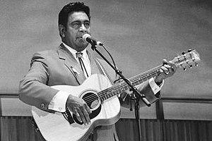 Um homem é mostrado em um tiro superior do corpo, ele canta em um microfone, segurando uma guitarra acústica.