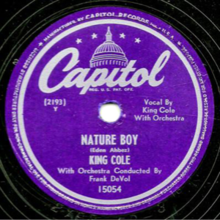 A black Gramophone disc on which the song and artist name is printed on violet paper