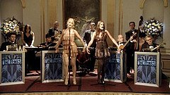 Two female vocalists perform on stage foreground to eight bandmates on the set of Gossip Girl.