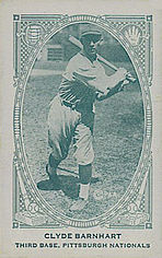 A man in a lightly colored baseball uniform swinging a bat.