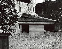 A black and white photo of a small triangular doghouse with a door on its left