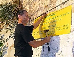"Zochrot - Eitan Bronstein, director of Zochrot, posts a sign in Hebrew and Arabic on the former Arab ""ghetto"" in Lod (Lydda), 2003."