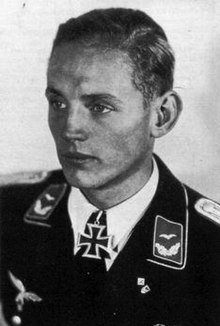 A black and white photograph of a young man wearing a military uniform looking off to the left wearing a neck order in shape of an Iron Cross.