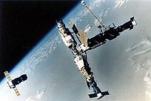 An image of a space station consisting of four modules arranged in a T-shape. A short, stubby module is docked to a longer, stepped-cylindrical module which has a number of docking ports arranged in a sphere at one end. Two other modules, similar in size, project from opposing ports on this sphere. A Progress spacecraft is docked to the short module, a Soyuz spacecraft to the end of the lower module in the crossbar of the T, and another Progress spacecraft is seen a distance away from the module cluster, carrying out undocking operations.