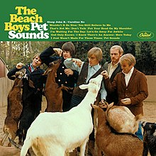 "The Beach Boys at the zoo feeding apples to goats. The header displays ""The Beach Boys Pet Sounds"" followed by the album's track list."