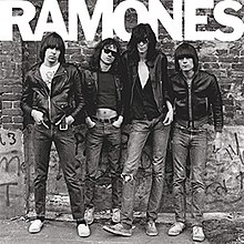 "Four men standing against a graffiti-covered wall. Each man has a black leather coat, blue jeans, and brown hair. At the top of the black-and-white image, ""RAMONES"" is spelled out in all caps."