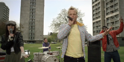 A young woman in a dark leather jacket, a man in a blue jumper, a man with bleached blonde hair in a yellow T-shirt and a man in a red leather jacket are performing on a grassy area outside a tower block estate during daytime. The man in the blue jumper is drumming at a drum kit; the other three are singing into microphones.