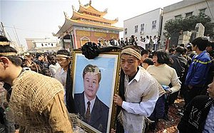 Procession led by some Asian people dressed in white/hemp carrying a photograph of a man in a suit.