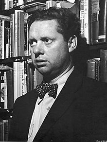 A black and white photograph of Thomas wearing a suit with a white spotted bow tie in a book shop in New York.