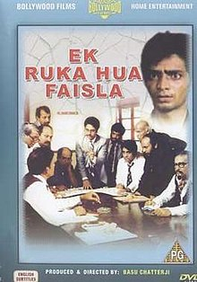 The image is a front-side view of DVD cover for film. It features eleven men at bottom around a round-table engaged in a discourse. At top the title of film appears, beside which there is face of another man.