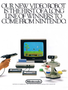 "A gameplay diorama featuring an NES prototype with top-loaded Famicom cartridge, AVS style controllers, and R.O.B. It has the caption ""Our new video robot is the first of a long line of winners to come from Nintendo""."