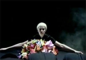 """Ice Hockey Hair - The music video for """"Smokin'"""" features a woman dressed in black with a blonde bob haircut watching over a group of people wearing berets while they make origami animals. In this screenshot the woman piles up the origami creatures while the beret wearers, shown in the foreground, bow their heads."""