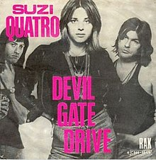 "The front cover of Suzi Quatro's single Devil Gate Drive. Quatro is standing in the centre with her right hand on her hips and the other hand behind her. Standing behind her, on either side, are two members of her band. She is wearing a leather jacket, jeans, and many necklaces. The cover is in black and white with the words ""Suzi Quatro"" and ""Devil Gate Drive"" in hot pink."