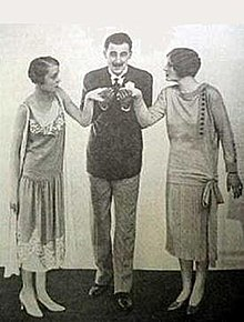 smart youngish man in blazer, kissing the hands of two youngish women either side of him