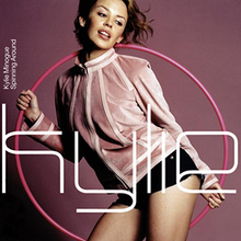 "A woman dressed in a rose-coloured jacket and black hot-pants is striking a pose in front of a dark purple background with a pink hoop in her hand. The word ""Kylie"" is written in front of her in a large white font."