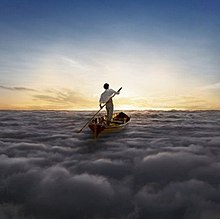 A man in a white shirt and brown shorts stands in a Gondola at the center of the image. He rows the Gondola across a sea of clouds, heading towards a sunset.