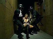 A woman, who wears a golden coat and boots, is pulled and lifted off the floor by two police officers wearing black suits.