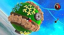 Nesta captura de tela, Mario está correndo por um pequeno planetóide circular no espaço sideral.  O jogo possui uma mecânica de gravidade que permite ao Mario correr de cabeça para baixo ou de lado.