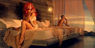 """California King Bed - A scene from the video, where Rihanna and her suitor sit at opposite ends of a """"California King Bed"""", signifying that although they are in the same bed, they are a distance away from each other."""