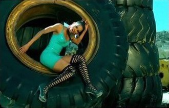 "Work (Ciara song) - Ciara posing in a tire while sporting a turquoise dress in the music video for ""Work"""