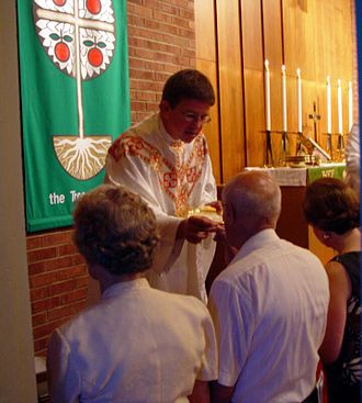 Closed communion - Celebration of the Holy Eucharist in a parish of the Lutheran Church–Missouri Synod, with communicants kneeling at the chancel rails to receive the body of Christ.