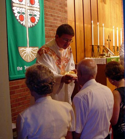 A Lutheran priest administers the Eucharistic elements to the faithful during the celebration of the Holy Mass. Communion3.jpg