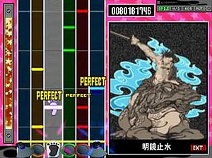 GuitarFreaks and DrumMania - The Drum Mania gameplay screen. The left is the gameplay area, the right shows a video often related to the song.