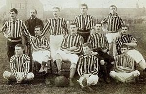 Eleven young men in striped shirts and plain shorts and one older man wearing a suit pose for a team photo. Three sit on the floor, two cross-legged. Four sit on chairs behind, each in a different, casual pose. One has his foot on a football. At the back, the older man and the remaining young men stand, hands on hips or resting on the chairs.