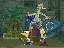 Two cartoon boys stand beside each other looking in opposite directions. A cartoon girl with red hair stands clumsily on their heads, wrapped in raggy toilet paper. Behind them are pipes, a gray brick wall, and signs.