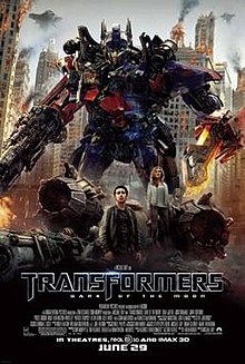 The poster depicts a Transformer named Optimus Prime, standing with a blade in his left arm, and a blaster in his right arm. There is also a young couple standing below the Transformer, and just where the 3 are standing, there is also a crash-landed Decepticon fighter. Behind the Transformer and the couple, there is a war-torn city of Chicago, with Decepticon battleships surrounding it. The film title and credits are on the bottom of the poster.