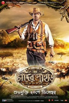 An young man of Indian origin is looking back with a rifle on his shoulder, having a backdrop of jungle, animals, mountain ranges and the logo art of the film