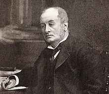 Head and upper body of a middle-aged man with receding hair, clean shaven, wearing a wing collar with tie, looking left. He is seated at a table, with a pen in his right hand.