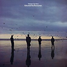 An album cover showing four men in silhouette standing on a wet beach. There are dark clouds in the sky and the sun is low on the horizon. The album's name and the band's name is in white letters in the top centre of the album cover.