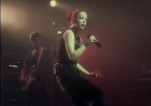 """When I Grow Up (Garbage song) - Vocalist Shirley Manson and bassist Daniel Shulman performing """"When I Grow Up"""" onstage in the music video."""