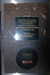 A plaque with words enclosed in a square box, underneath which is a square metal inside a circle.
