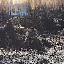 "A train trestle covered in thick kudzu with ""R.E.M. / MURMUR"" written in blue"
