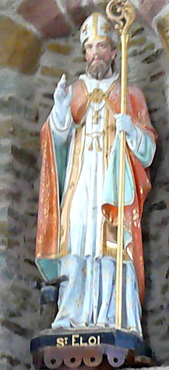 """Saint Eligius - Statue of St. Eligius (in French, """"St. Eloi"""") in the church of St. Marcel in St. Marcel (Aveyron), France. At the saint's right foot, note the tools of his original trade."""