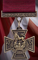 A bronze cross pattée bearing the crown of Saint Edward surmounted by a lion with the inscription Pro Valore. A crimson ribbon is attached