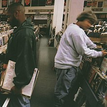 Two men look through vinyl albums at a record store.