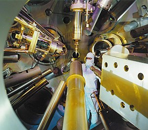 "Maintenance on the Nova target chamber. The various devices all point towards the center of the chamber where the targets are placed during experimental runs. The targets are held in place on the end of the white-colored ""needle"" at the end of the arm running vertically down into the chamber."
