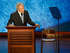 Man in coat and tie stands at a podium, looking towards a chair.