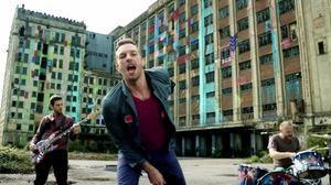 Every Teardrop Is a Waterfall - Screenshot from the music video, which shows the band playing across various backdrops sprayed with colourful graffiti paint.