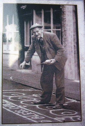 Cheshire - A resident of Knutsford sanding the street in celebration of May Day 1920. The custom continues to this day.